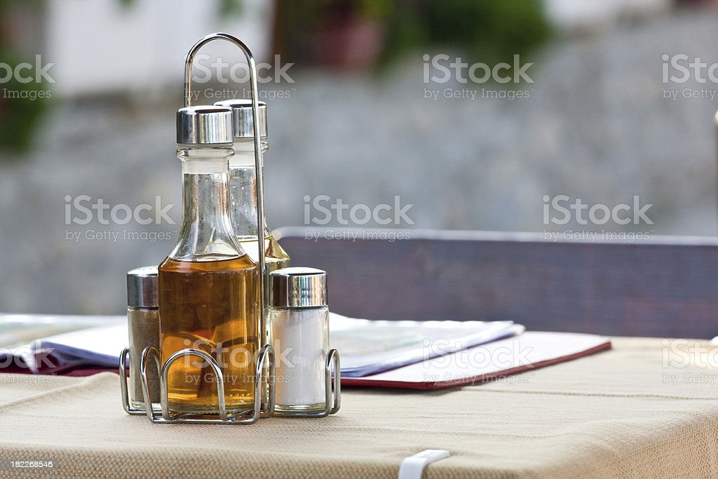Bottles with olive oil, vinegar, salt on the table royalty-free stock photo