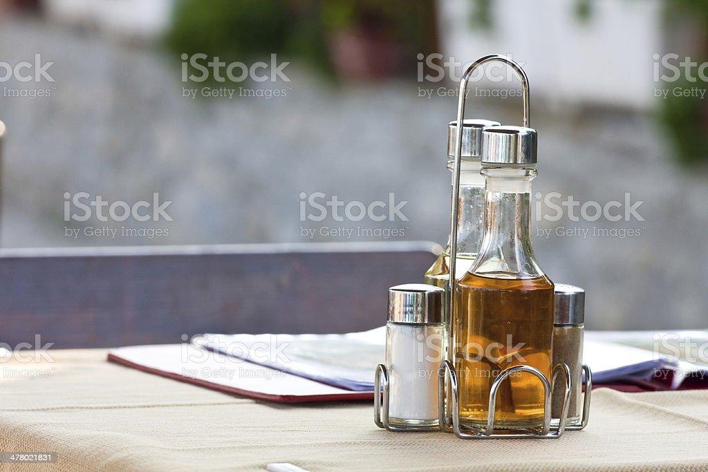 Bottles with olive, vinegar, salt on the table in restaurant royalty-free stock photo