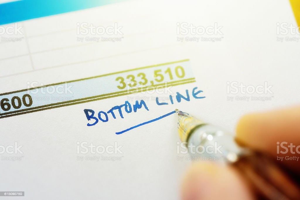 'Bottom Line'  being written in ink on a financial document stock photo
