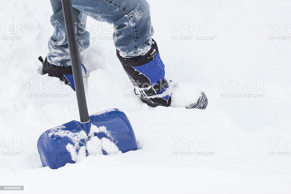 bottom torso of male wearing winter boots in the snow stock photo