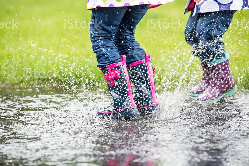 Bottom View of Two Young Girls Jumping in Water Puddle stock photo