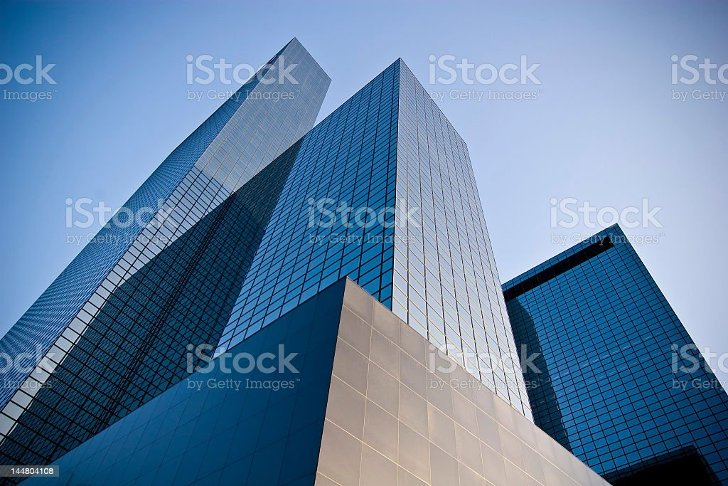 Bottoms up view of three skyscrapers and a blue sky stock photo