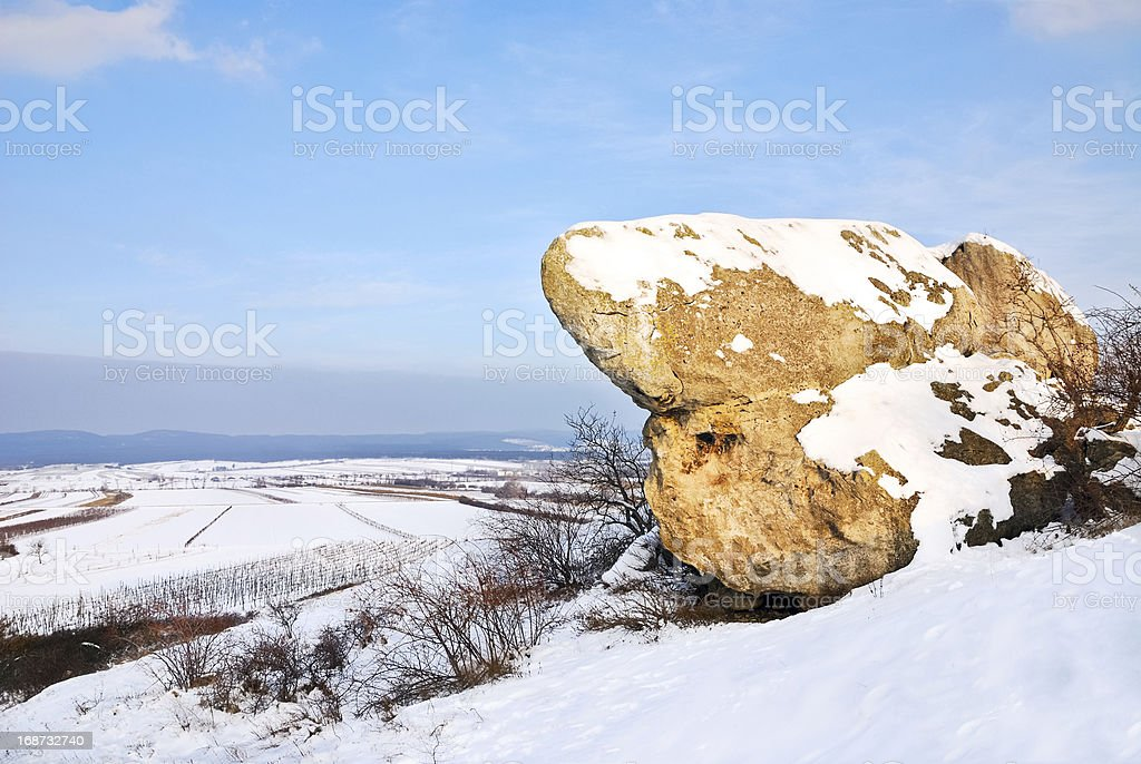 Boulder in snowy landscape stock photo