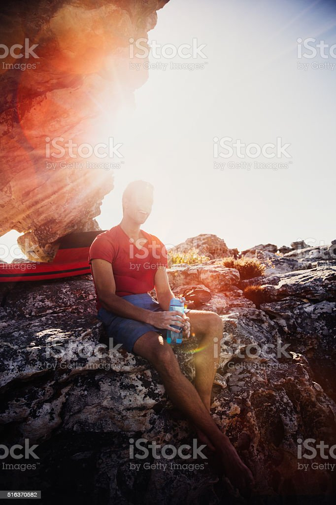 Bouldering man resting on rock from climbing with sun flare stock photo