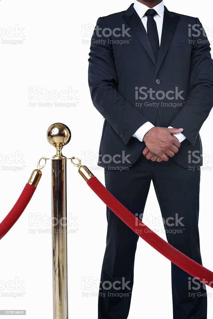 Bouncer in suit standing behind crowd control post against white stock photo