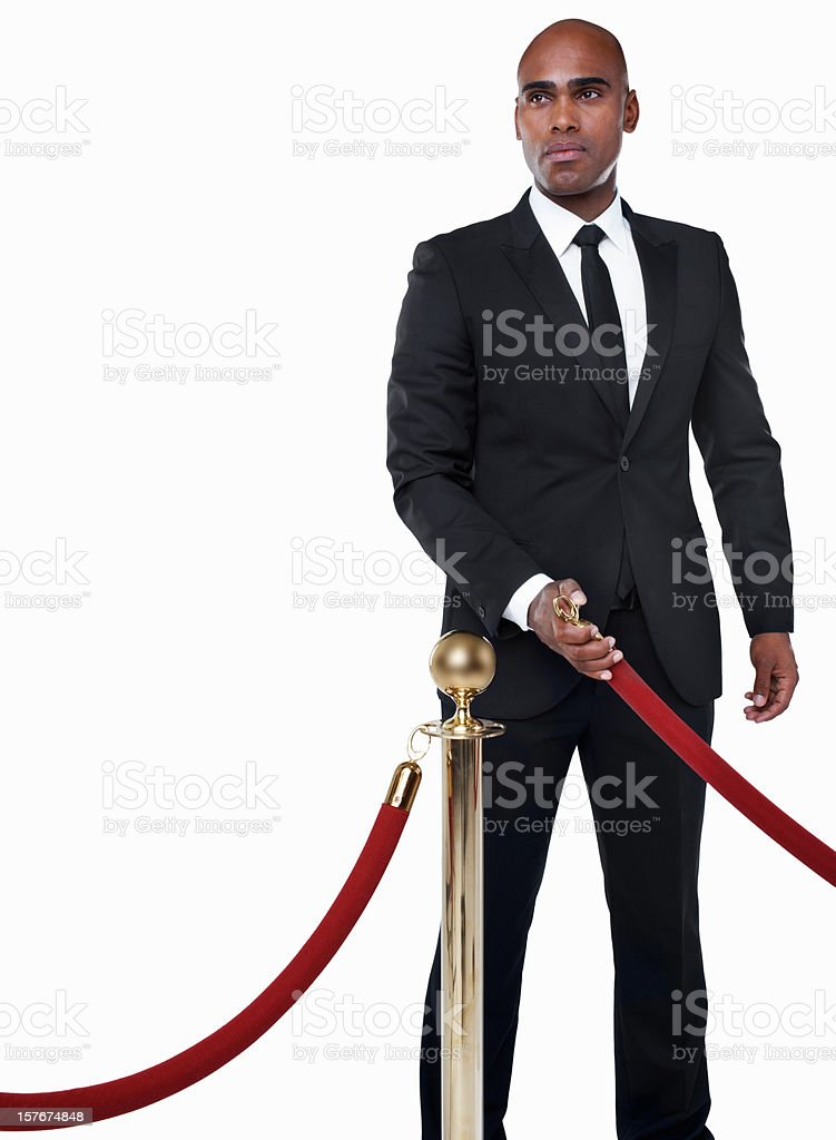 Bouncer in suit with crowd control post against white stock photo
