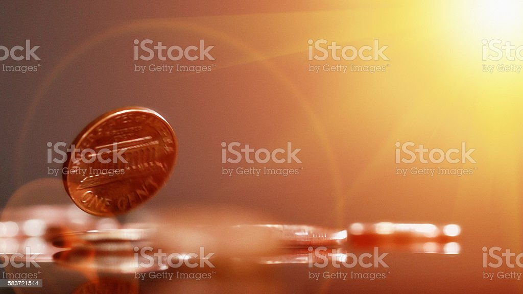Bouncing cash: US 1c coin falling against gold-toned background stock photo