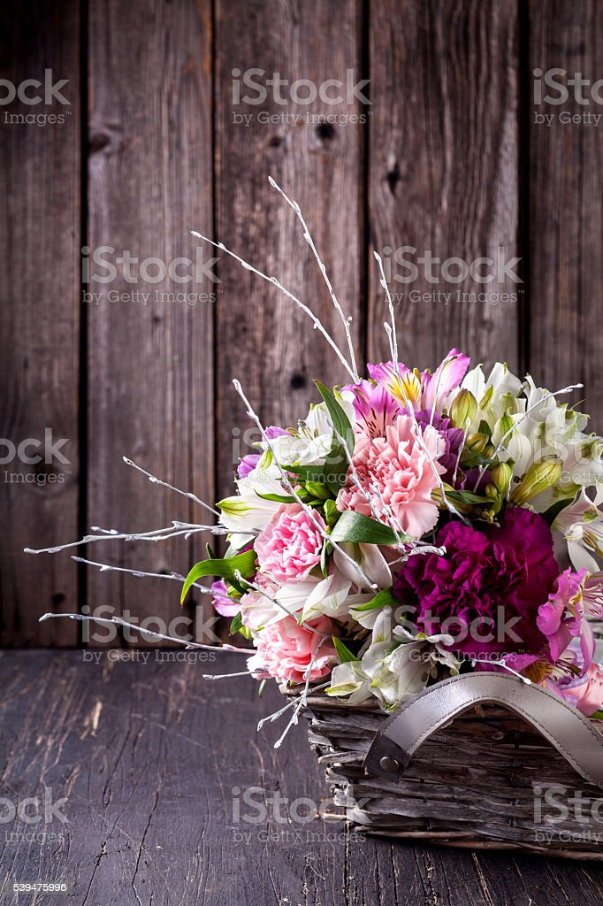 Bouquet from gillyflowers and alstroemeria in the basket on old stock photo