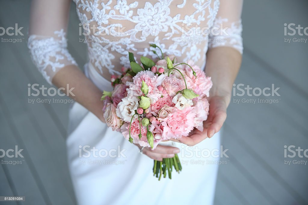 Bouquet in the hands of the woman in white stock photo