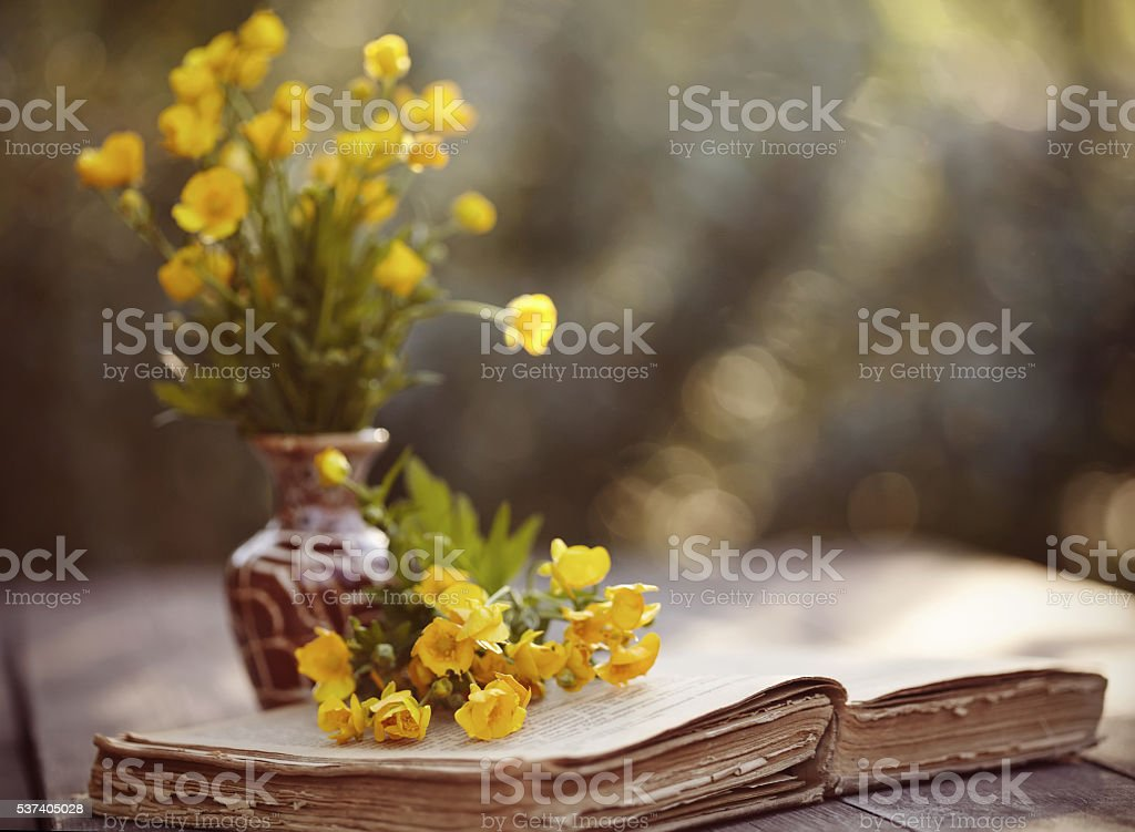 Bouquet of buttercups and the old book on a table. stock photo