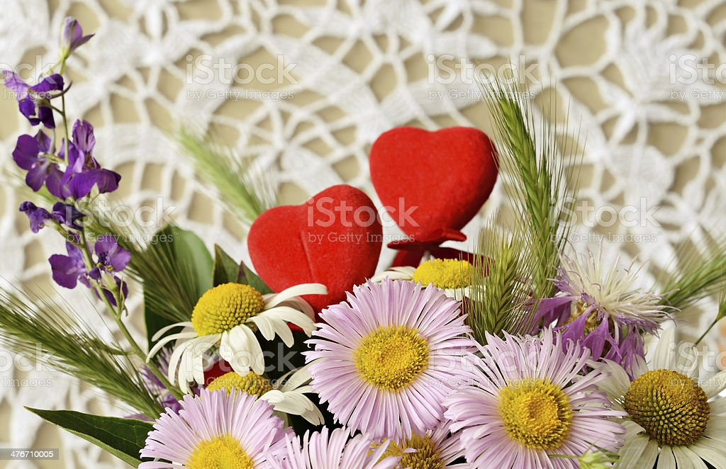 Bouquet of chamomiles and two hearts royalty-free stock photo