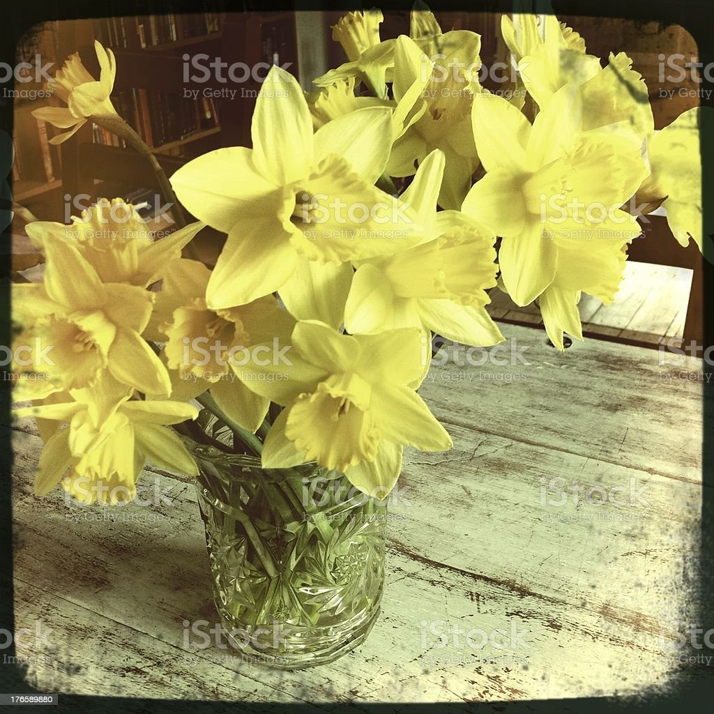 Bouquet of daffodils in a vase on an old table royalty-free stock photo
