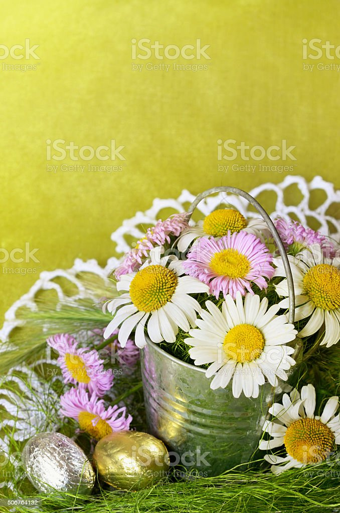 Bouquet of daisies in a metal bucket and shocolate eggs stock photo