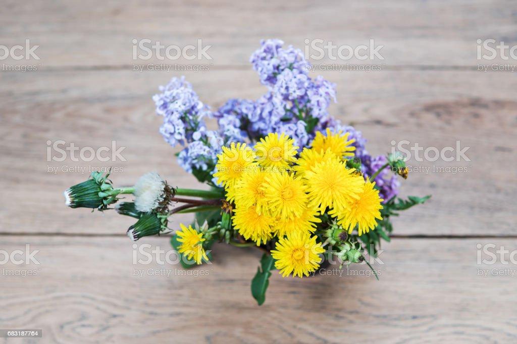 Bouquet of dandelions and purple lilacs stock photo
