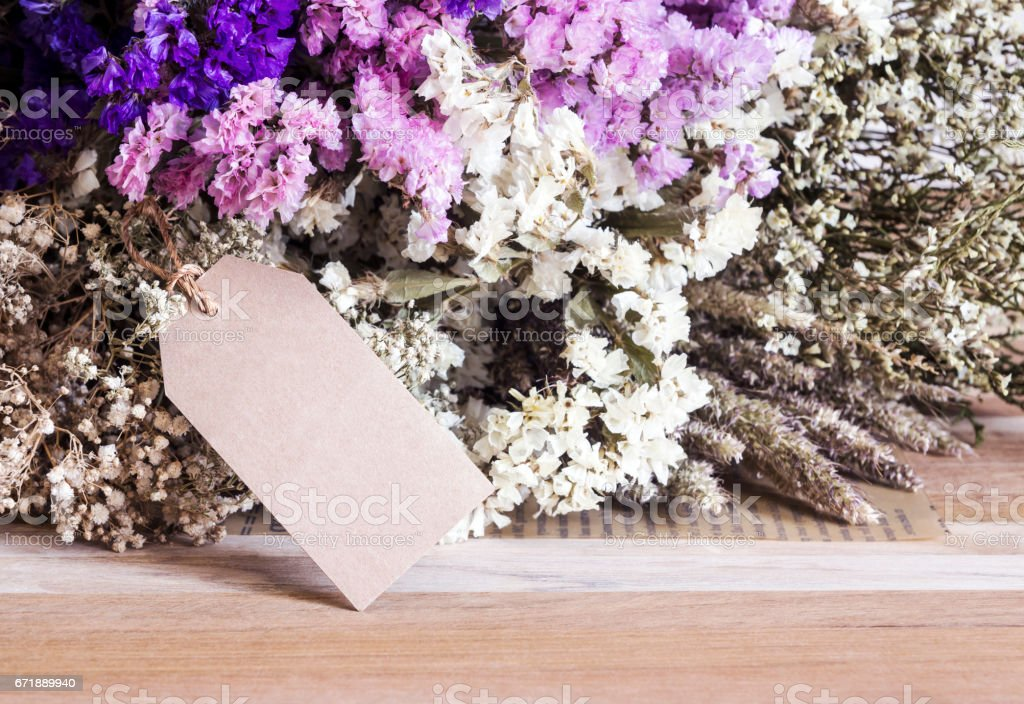 Bouquet of dried flowers with blank paper tag on the wooden table stock photo