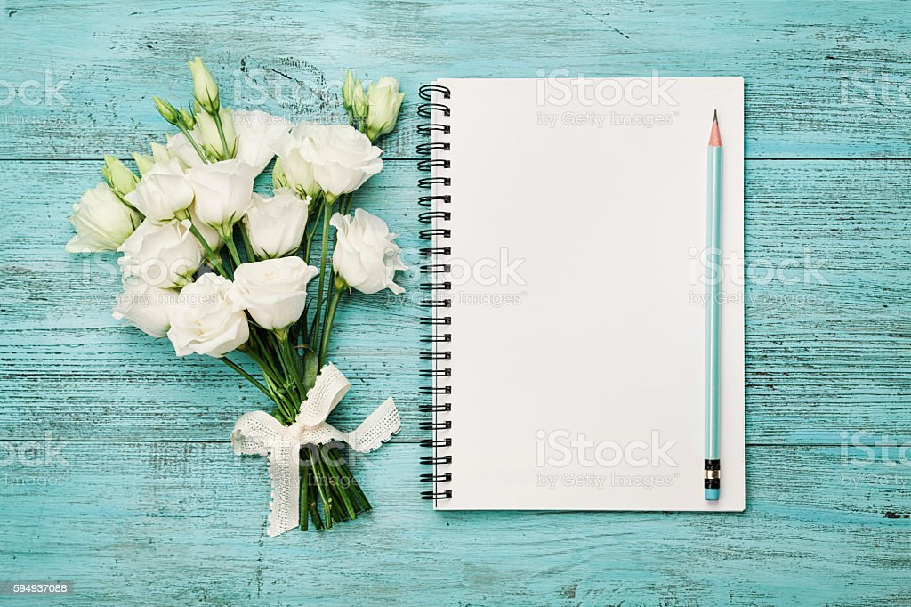 Bouquet of flowers and empty paper sheet. Planning. Flat lay. stock photo