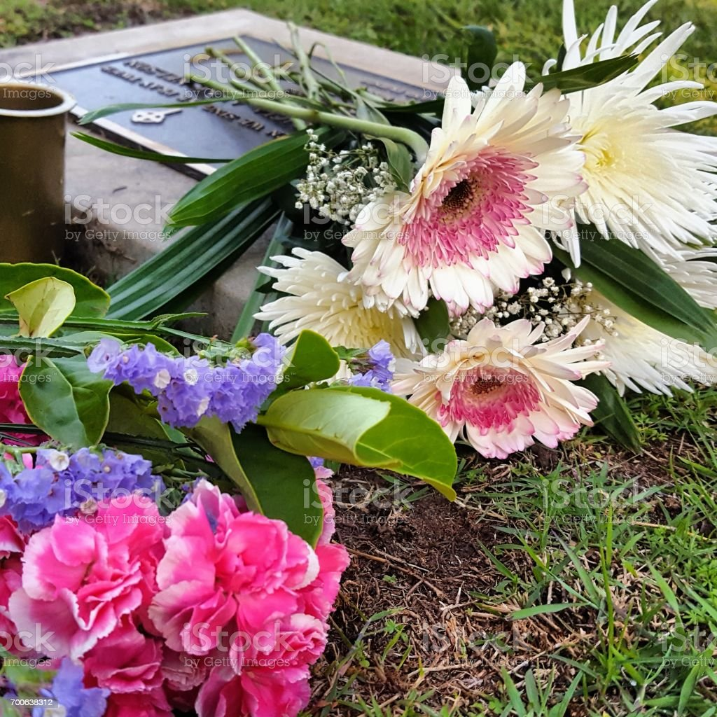 Bouquet of flowers on gravestone stock photo