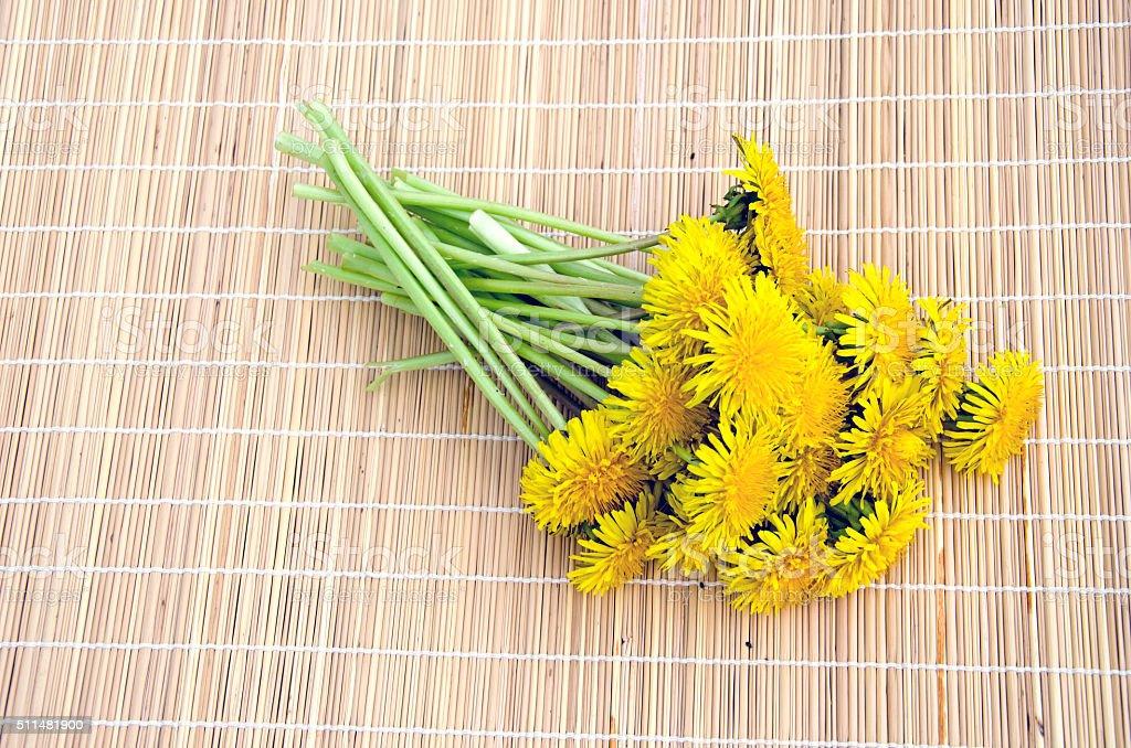 Bouquet of fresh dandelions on bamboo mat stock photo