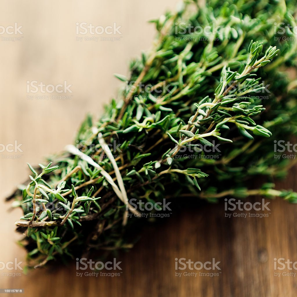 A bouquet of fresh thyme on a wooden surface stock photo
