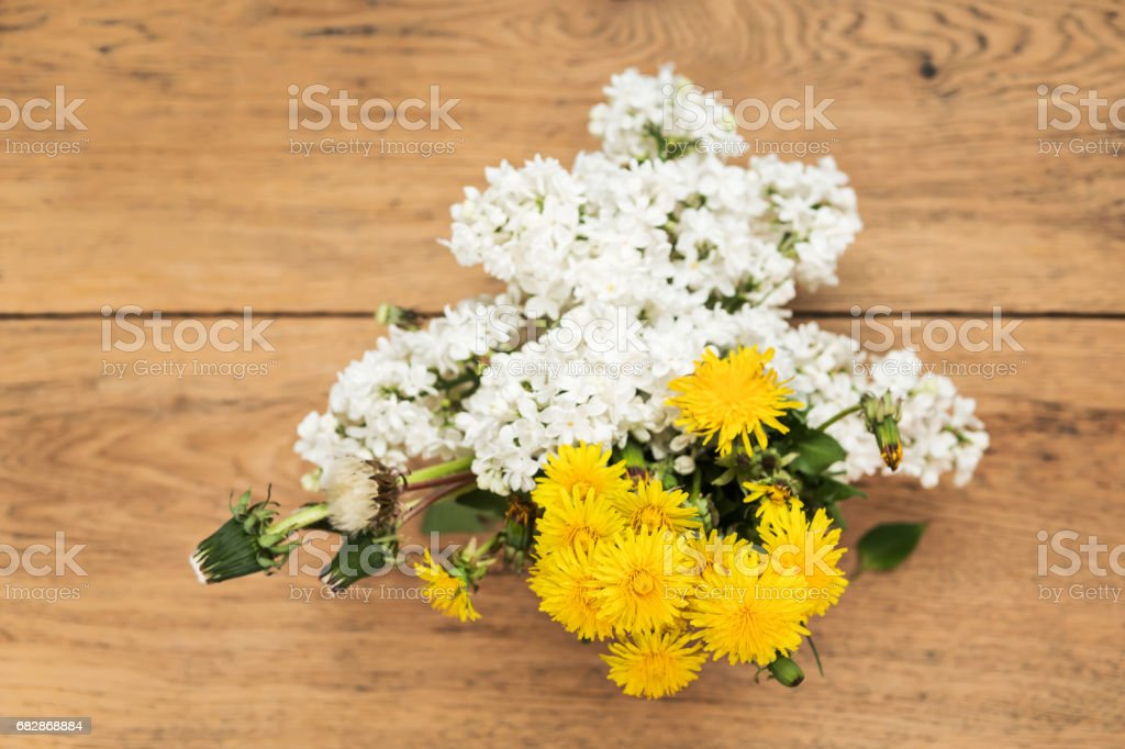 Bouquet of lilac and dandelions on the table stock photo
