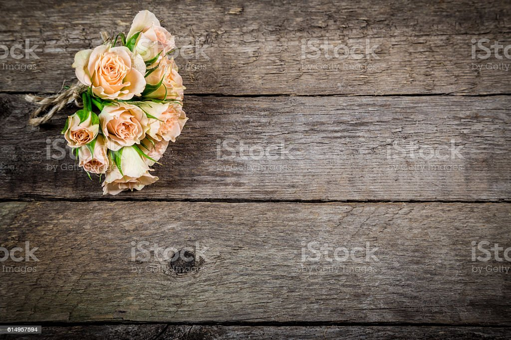 Bouquet of little beige roses on wooden background stock photo