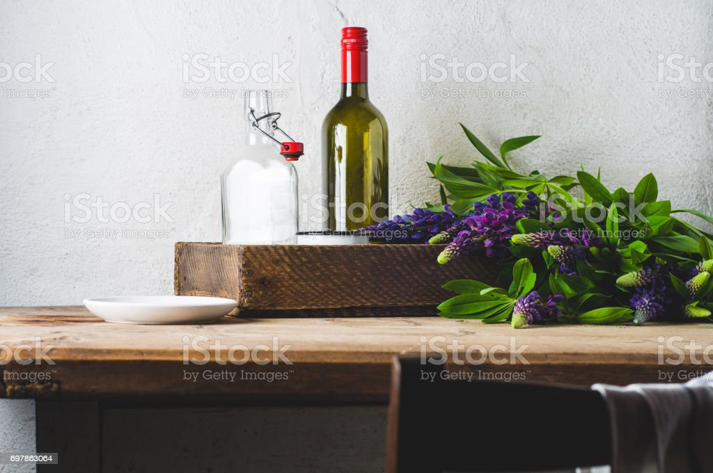 Bouquet of lupines and ware on an old wooden table against the background of a white concrete wall stock photo