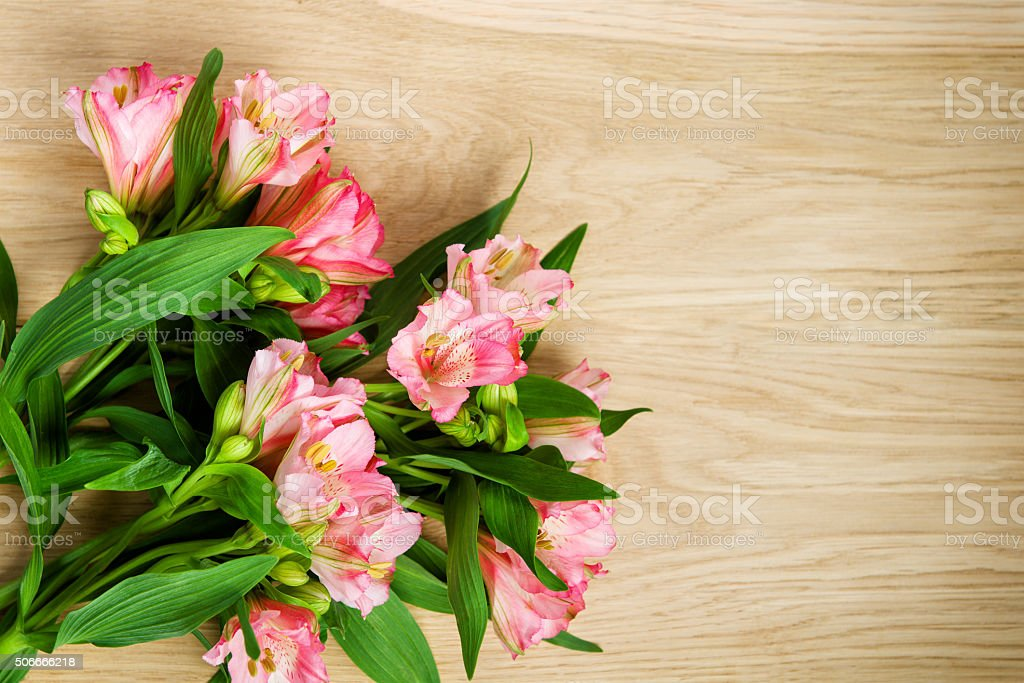 bouquet of pink alstroemeria on wooden plate stock photo