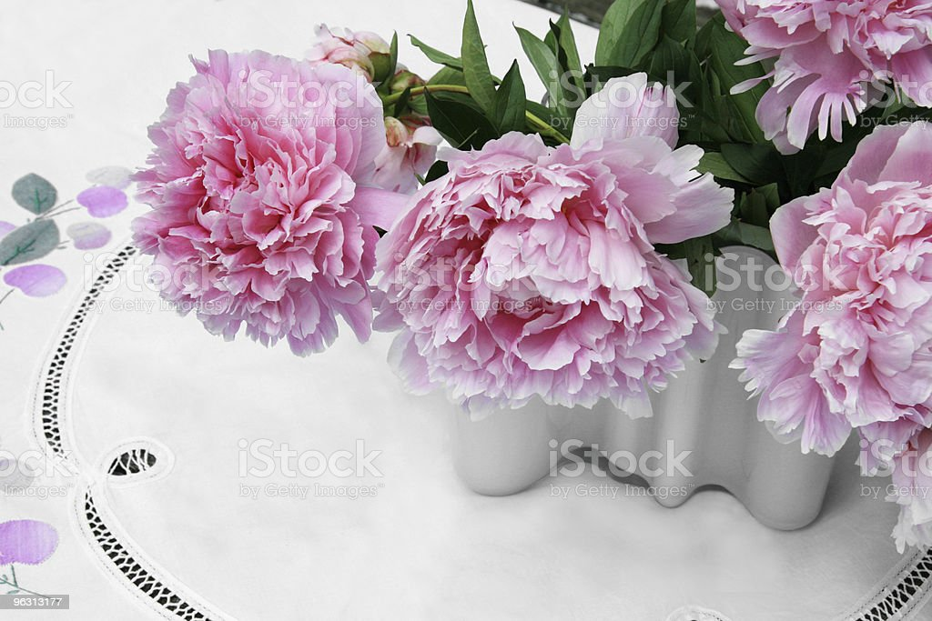 Bouquet of  pink peonies in a white glass vase stock photo