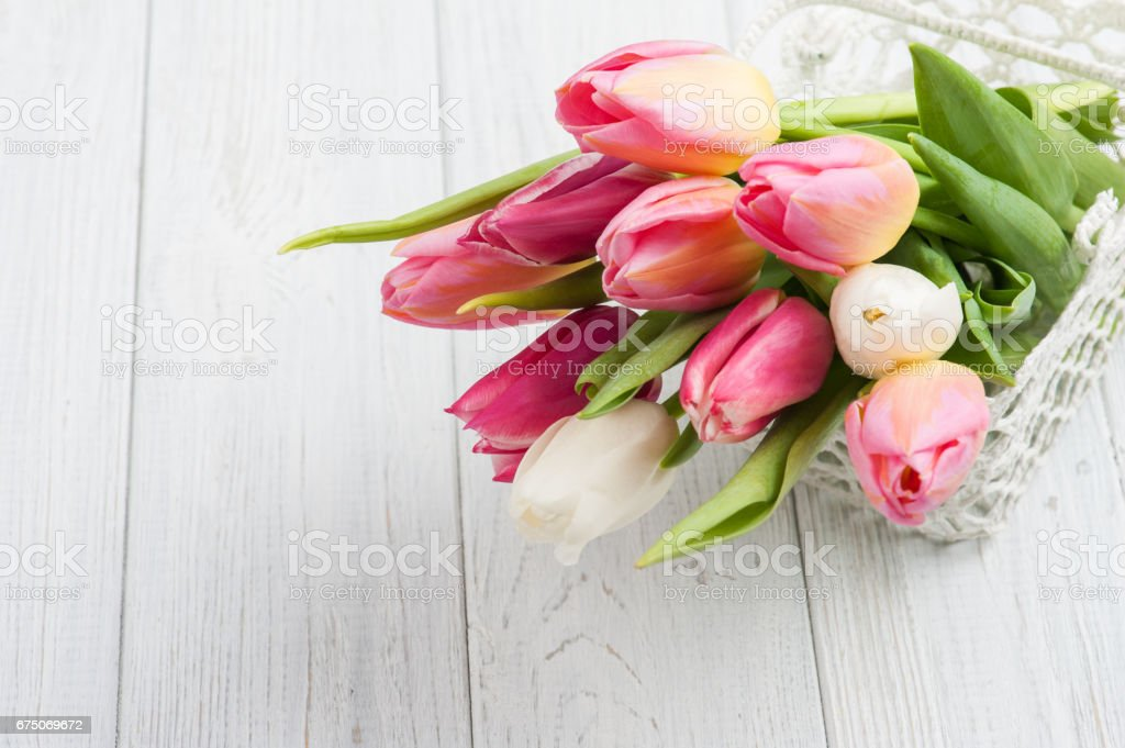 Bouquet of pink tulips in crochet basket stock photo