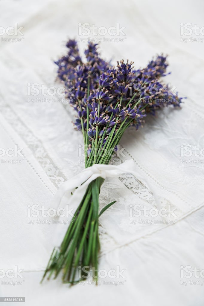 Bouquet of purple lavender tied with ribbon on lace cloth stock photo
