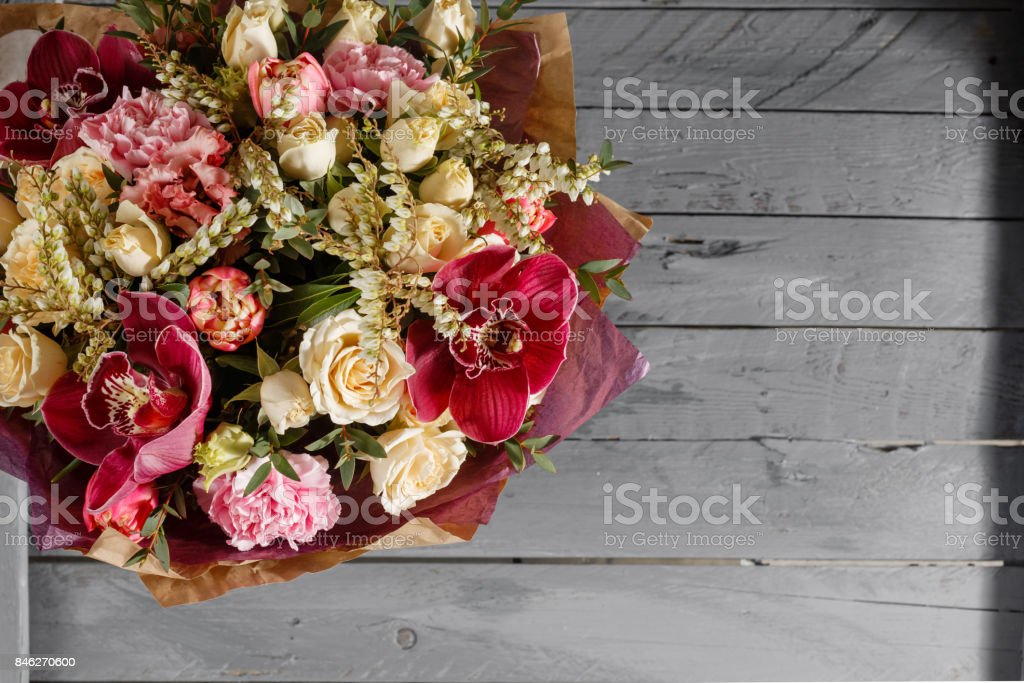 Bouquet of Purple Orchid and Other colors flowers on wooden background, In the basket. copy space. stock photo