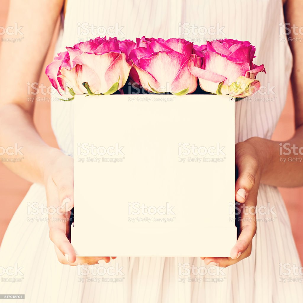 Bouquet of pink roses in a box in the hands of the girl.