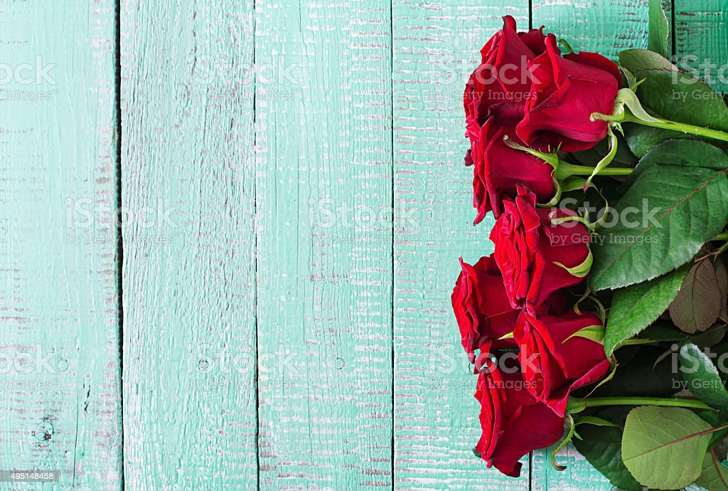 Bouquet of red roses on a light wooden background stock photo