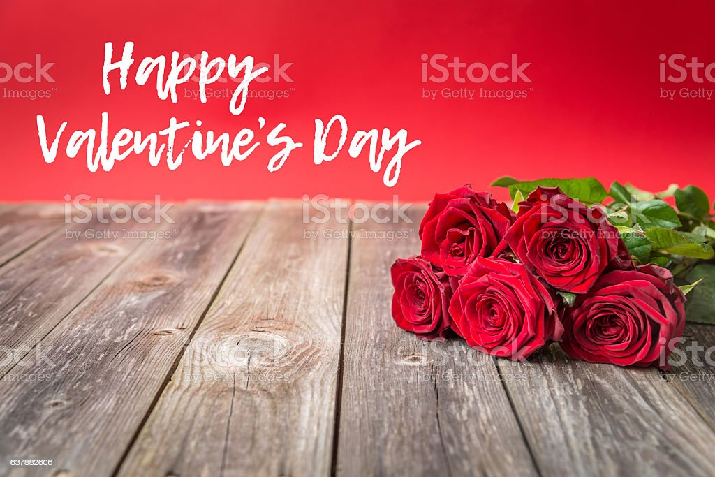 bouquet of red roses on wood background. Valentines Day stock photo