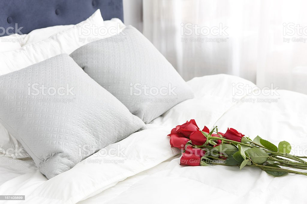 Bouquet of Red Single Roses on White Bedspread, Copy Space stock photo