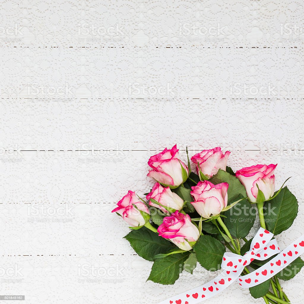 Bouquet of roses on white crochet tablecloth. Top view stock photo