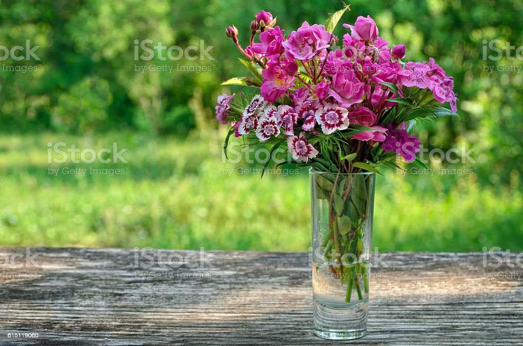 Bouquet of small carnations on a table in the garden stock photo