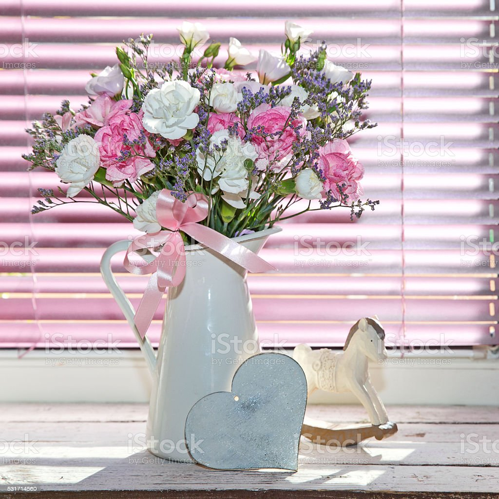 Bouquet of summer flowers in glass vase near the window stock photo