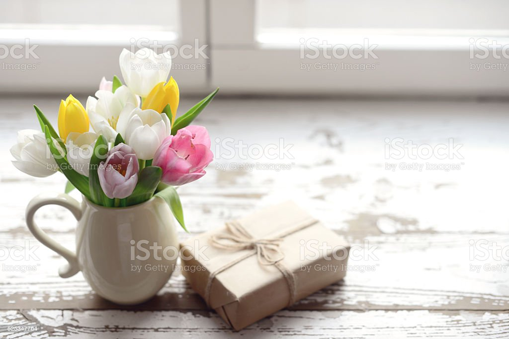 bouquet of tulips in a vase and gift box stock photo