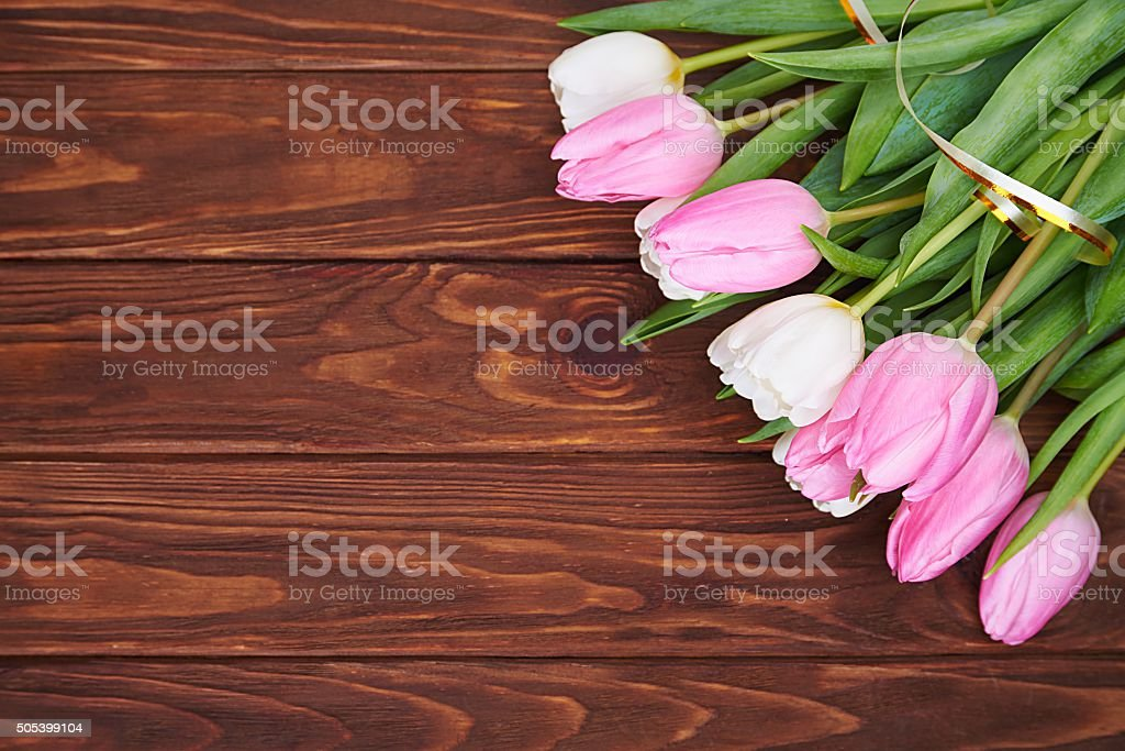Bouquet of tulips on dark wood table. stock photo