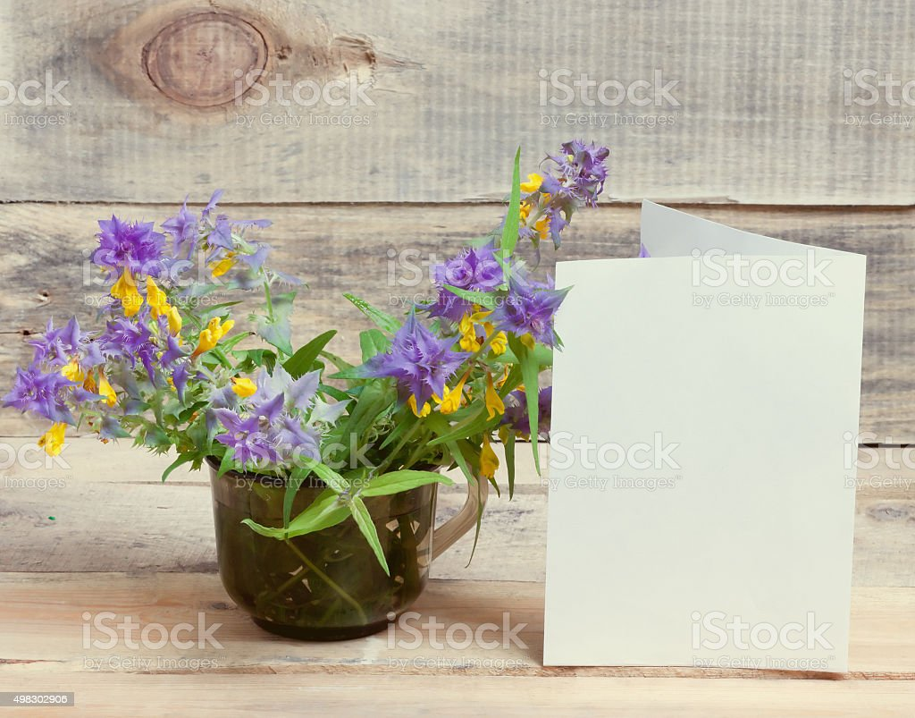 bouquet of wild flowers and a blank sheet of paper stock photo
