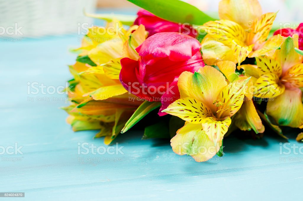 Bouquet  yellow, red spring flowers on vintage blue wood background. stock photo