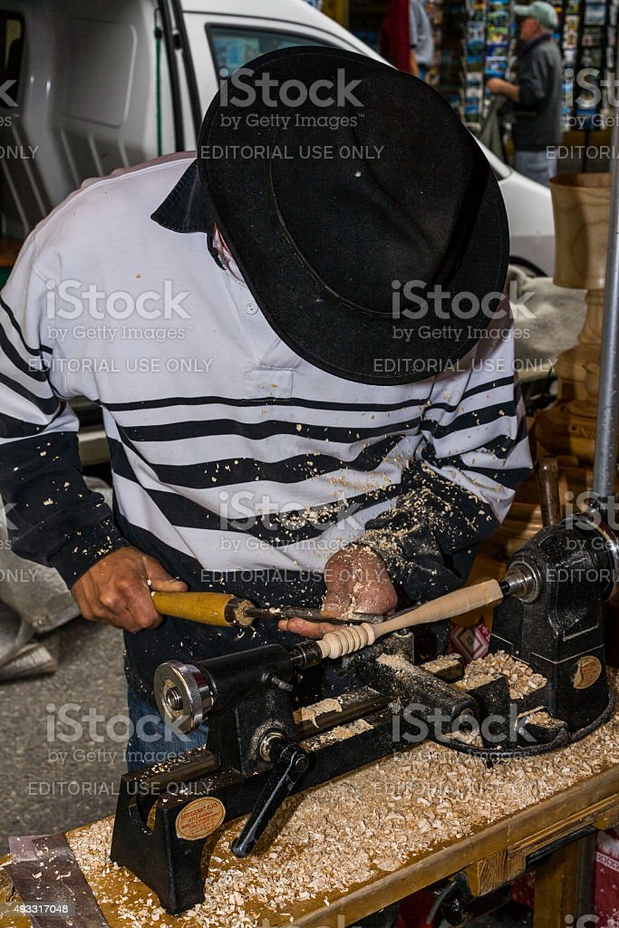 Bourg-Saint-Maurice, France. Craftsman carving wooden objects during a craft fair stock photo