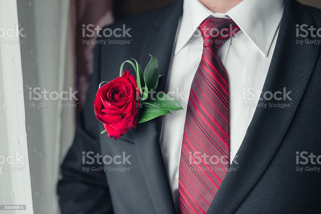 boutonniere of red roses on the bride jacket closeup stock photo