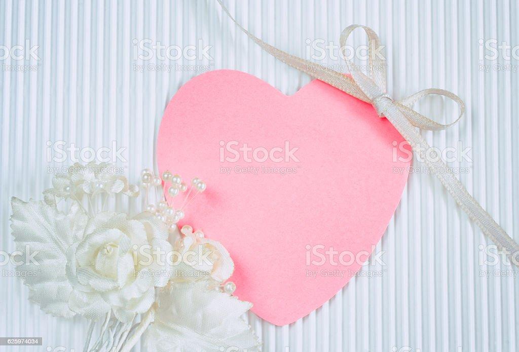 boutonniere, pink heart shaped tag, white silk ribbon stock photo