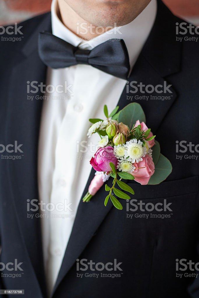 boutonniere pinned on man in black suit stock photo