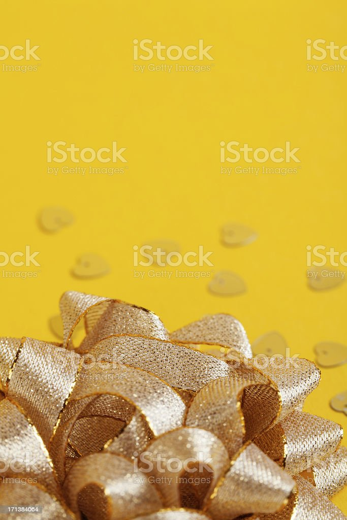 Bow and confetti on yellow background stock photo