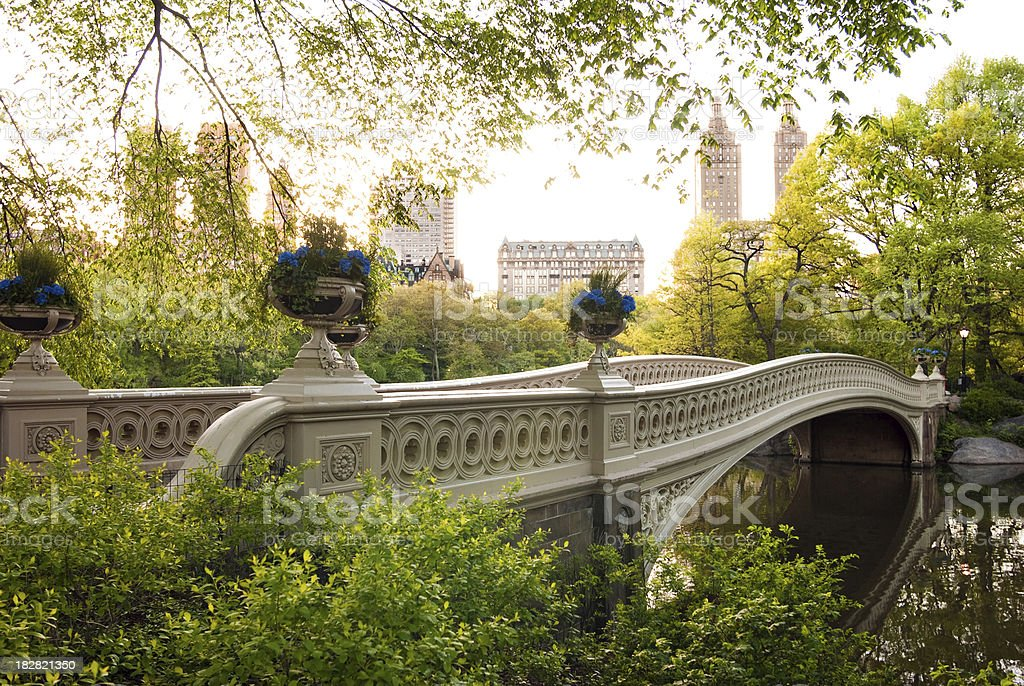 Bow Bridge at Central Park with buildings in background stock photo