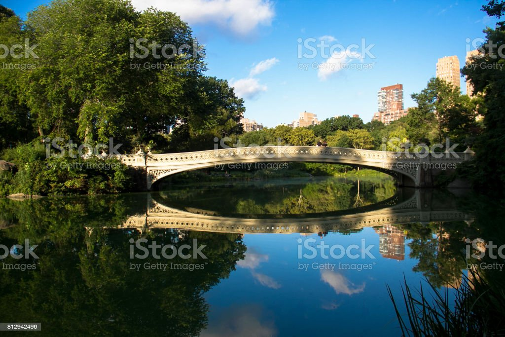 Bow bridge clearly reflects on the calming lake at Central Park with sky stock photo