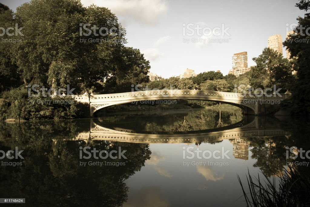 Bow bridge clearly reflects on the lake at Central Park with sky in vintage style stock photo